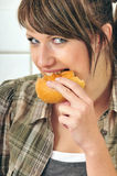 Muchacha linda que come un rodillo de pan fotografía de archivo libre de regalías