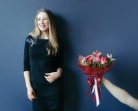 Muchacha linda que consigue el ramo de tulipanes rojos Novio que da tulipanes Fotos de archivo libres de regalías
