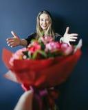 Muchacha linda que consigue el ramo de tulipanes rojos Novio que da tulipanes Imagen de archivo