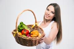 Muchacha linda que da la cesta con las frutas en la cámara Foto de archivo