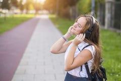 Muchacha linda que disfruta de música con los auriculares al aire libre Relájese Imagen de archivo