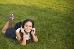 Muchacha linda que disfruta de música con los auriculares mientras que miente en la hierba Con el espacio para el texto Imagenes de archivo