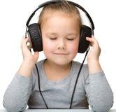 Muchacha linda que disfruta de música usando los auriculares Fotos de archivo libres de regalías