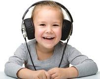 Muchacha linda que disfruta de música usando los auriculares Fotografía de archivo
