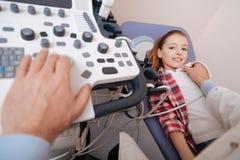 Muchacha linda que disfruta del examen del ultrasonido en el hospital Fotos de archivo
