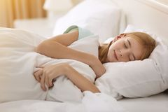 Muchacha linda que duerme en la almohada blanca Foto de archivo