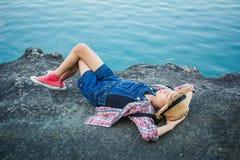 Muchacha linda que duerme en la roca en naturaleza Imagenes de archivo