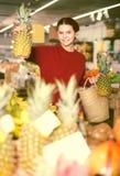 Muchacha linda que elige la piña en el mercado Imagen de archivo