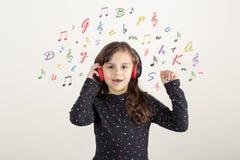 Muchacha linda que escucha la música con el auricular y que canta libre illustration
