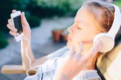 Muchacha linda que escucha la música con los auriculares al aire libre Imagen de archivo