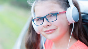 Muchacha linda que escucha la música con los auriculares al aire libre Imagenes de archivo
