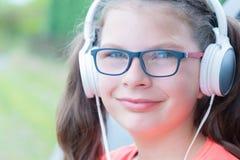 Muchacha linda que escucha la música con los auriculares al aire libre Foto de archivo libre de regalías