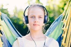 Muchacha linda que escucha la música con los auriculares al aire libre - mirada de a Fotos de archivo libres de regalías