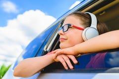 Muchacha linda que escucha la música con los auriculares - mirando a través de o Fotos de archivo