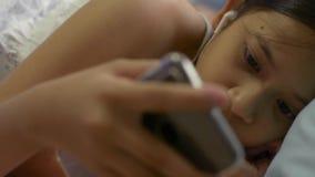 Muchacha linda que escucha la música del teléfono móvil con los auriculares que mienten en la cama almacen de video