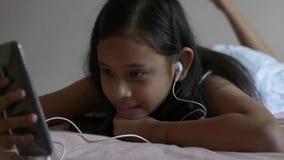 Muchacha linda que escucha la m?sica del tel?fono m?vil con los auriculares que mienten en la cama almacen de metraje de vídeo