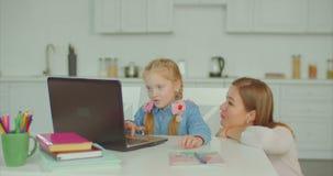 Muchacha linda que estudia con el ordenador portátil con la ayuda de la madre almacen de video