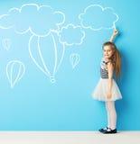 Muchacha linda que hace dibujos de tiza Foto de archivo libre de regalías