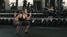 Muchacha linda que hace ejercicios en el bacground del gimnasio almacen de video