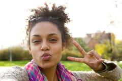 Muchacha linda que hace la cara de la diversión con el signo de la paz Fotografía de archivo libre de regalías