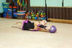 Muchacha linda que hace truco astuto con la bola en la gimnasia del arte Imágenes de archivo libres de regalías