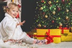 Muchacha linda que juega cerca de la chimenea y del árbol de navidad adornado Fotos de archivo libres de regalías
