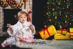 Muchacha linda que juega cerca de la chimenea y del árbol de navidad adornado Foto de archivo