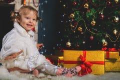 Muchacha linda que juega cerca de la chimenea y del árbol de navidad adornado Fotos de archivo