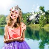Muchacha linda que juega con la vara mágica en el lago Foto de archivo