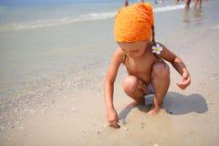 Muchacha linda que juega con los juguetes de la playa Imagenes de archivo