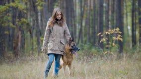 Muchacha linda que juega con su animal doméstico - pastor alemán en parque del otoño Fotos de archivo