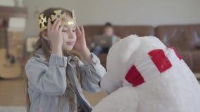 Muchacha linda que juega con un oso septentrional del juguete, vistiéndolo una corona y su hermano gemelo que juegan el ordenador metrajes