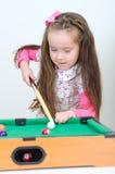 Muchacha linda que juega el billar Foto de archivo libre de regalías