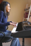 Muchacha linda que juega el piano Imagenes de archivo