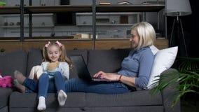 Muchacha linda que juega los juguetes mientras que mamá que trabaja en el ordenador portátil metrajes