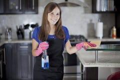 Muchacha linda que limpia la cocina Imagen de archivo libre de regalías