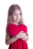 Muchacha linda que lleva a cabo el corazón del rojo de la felpa Fotos de archivo libres de regalías