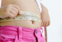 Muchacha linda que mide su estómago Imagenes de archivo