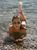 Muchacha linda que miente en el mar claro Fotografía de archivo libre de regalías