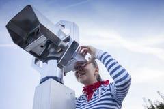 Muchacha linda que mira con los prismáticos de fichas Fotografía de archivo libre de regalías