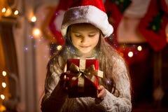 Muchacha linda que mira dentro de la caja del regalo de Navidad que brilla intensamente Fotografía de archivo libre de regalías