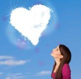 Muchacha linda que mira la nube blanca del corazón en el cielo azul Imagen de archivo