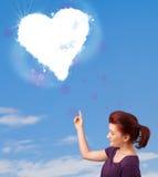 Muchacha linda que mira la nube blanca del corazón en el cielo azul Fotografía de archivo libre de regalías