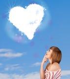 Muchacha linda que mira la nube blanca del corazón en el cielo azul Fotos de archivo libres de regalías