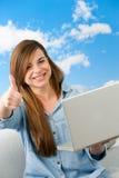 Muchacha linda que muestra los pulgares para arriba con la computadora portátil. Fotografía de archivo
