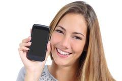 Muchacha linda que muestra una pantalla elegante en blanco del teléfono aislada Fotografía de archivo
