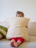 Muchacha linda que oculta detrás de la almohada Foto de archivo