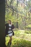 Muchacha linda que permanece cerca del árbol en parque del otoño Imagen de archivo