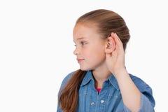 Muchacha linda que pincha encima de su oído imagenes de archivo