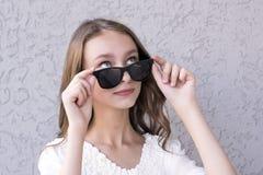 Muchacha linda que presenta en gafas de sol Imágenes de archivo libres de regalías